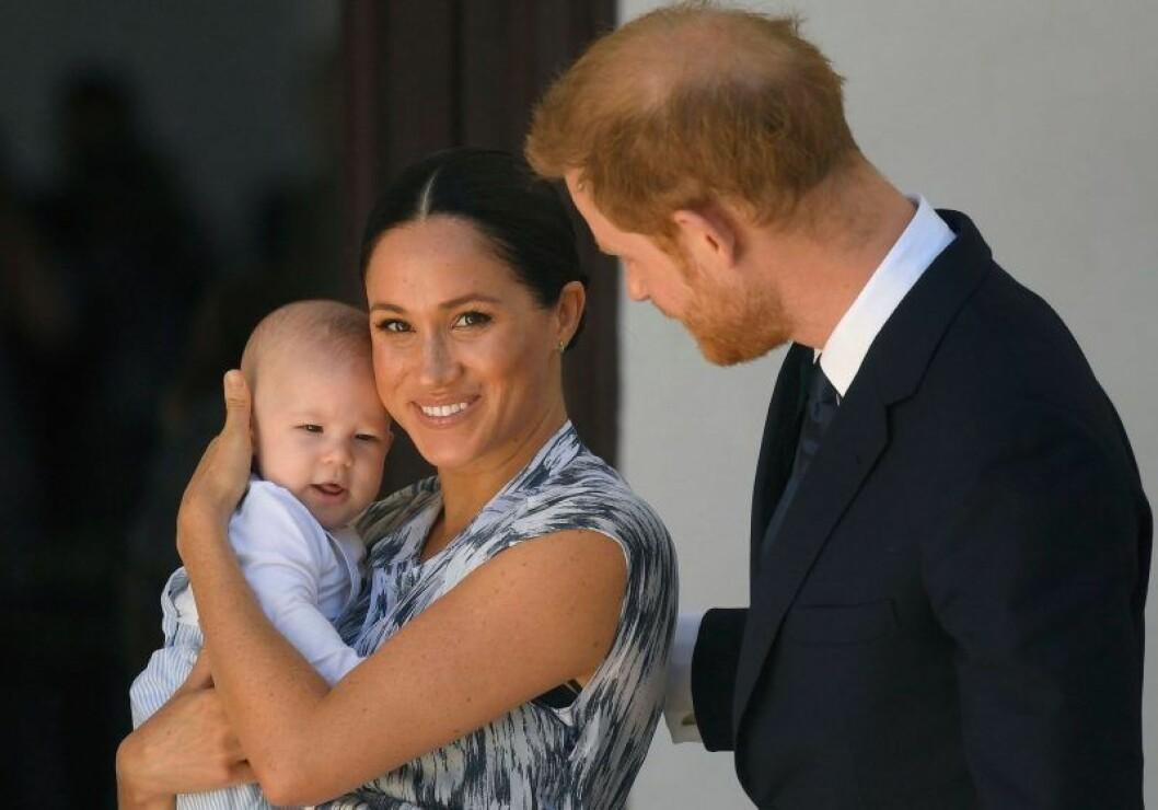 Meghan Markle håller sonen Archie och Harry står bakom och håller en hand på Meghans rygg