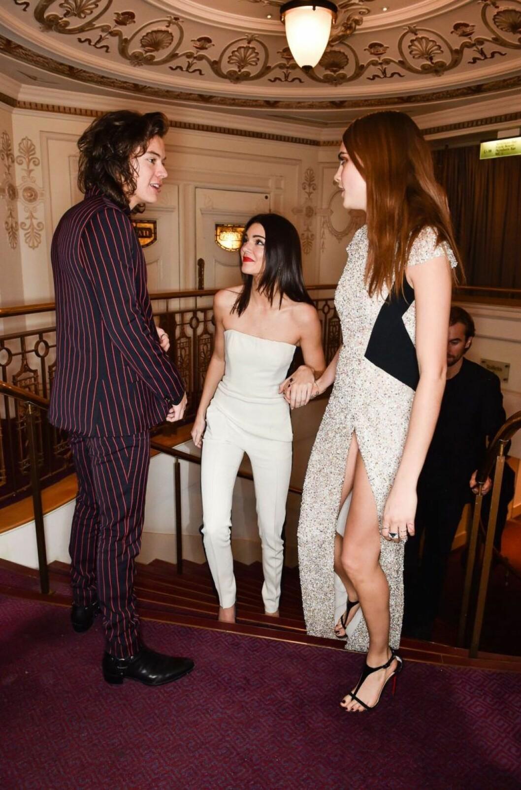 Harry Styles, Kendall Jenner och Cara Delevingne står i en trappa