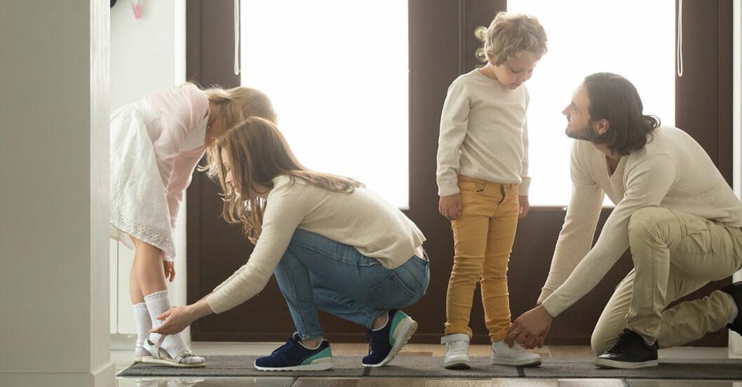 Föräldrar som hjälper barnen med skorna