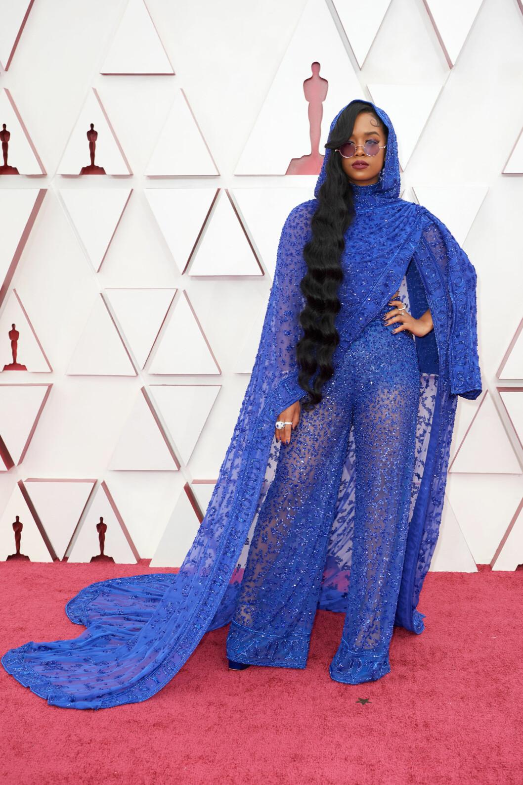 Sångerskan och låtskrivaren H.E.R. i långt hår och blå klänning