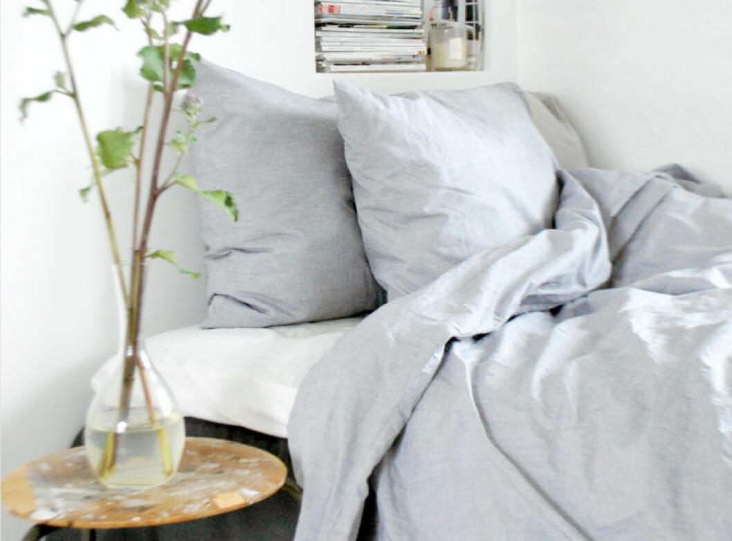 bäddad säng med ljusgrå linnelakan