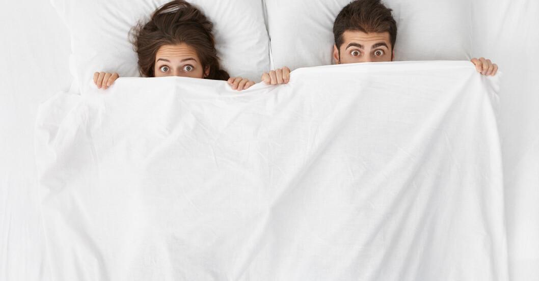 Brunhårig kvinna och man under täcke i säng
