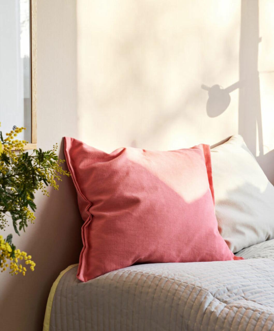 Trendigt sovrum med kuddar och överkast