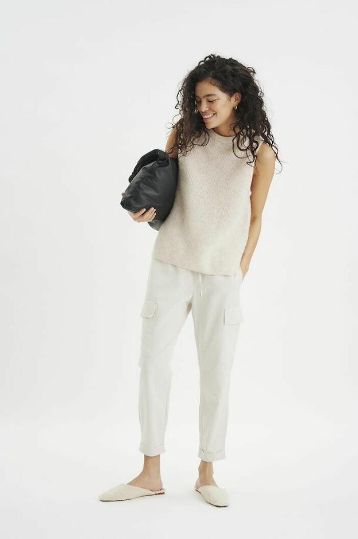 Gräddvitt, stickat linne med rundad hals. Stylat på modell ihop med vita byxor, gräddvita slip-ins och en svart kuvertväska. Linne från Inwear.
