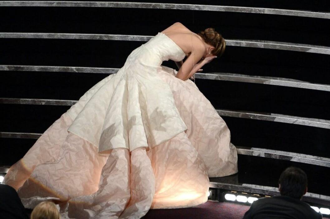 Jennifer Lawrence ligger i en trapp med en stor vit klänning