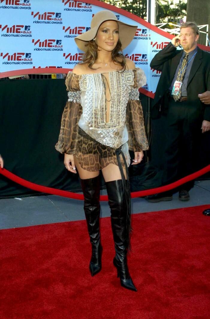 Jennifer Lopez i svarta lårhöga stövlar, leopardmönstrad tunika och en beige hatt på huvudet