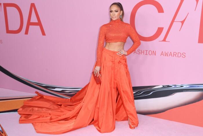 Jennifer Lopez i orange byxor med släp och en orange långärmad magtröja
