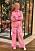 Jenny Strömstedt i ett set bestående av skjorta och byxor i orange och rosa mönster.
