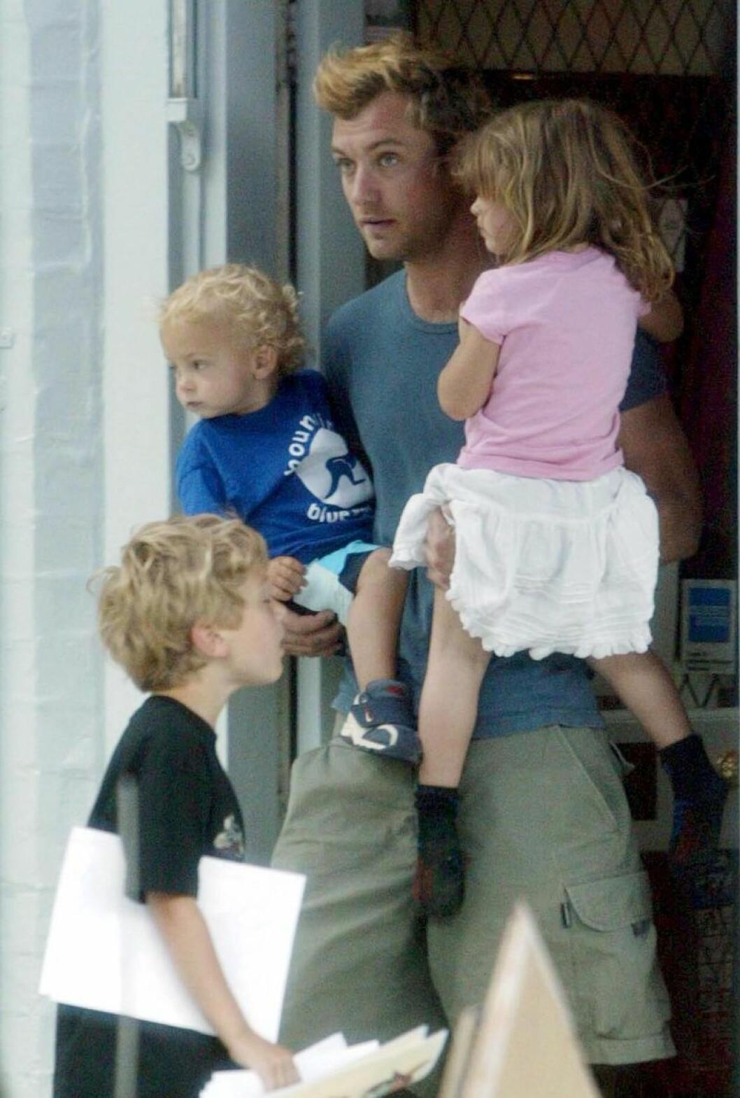 Jude law bär två barn och ett barn står framför honom