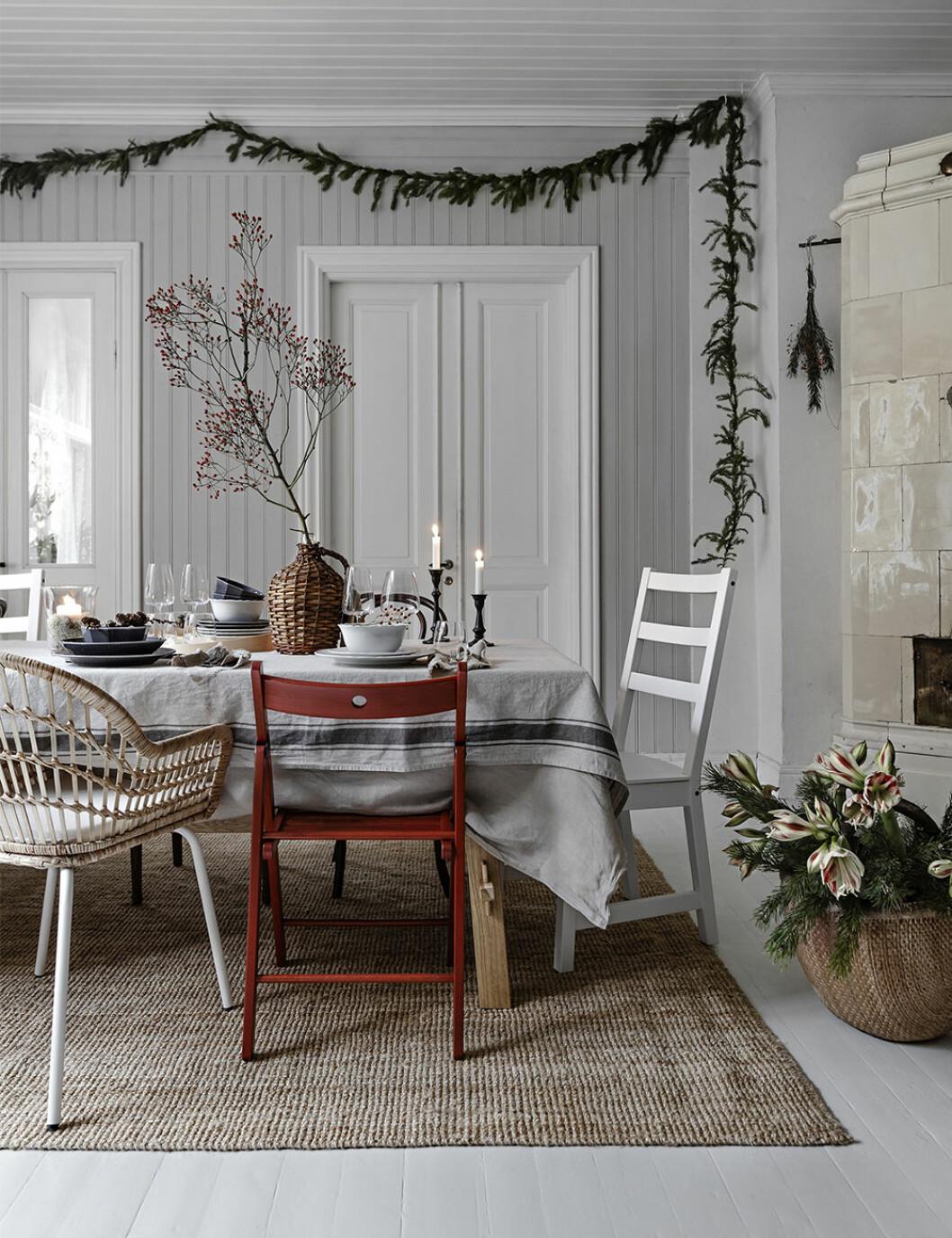 Julinredning med röd stol, girlang av granris och kvist med röda bär hos Ikea