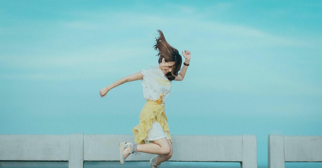 hoppande kvinna vid vattnet