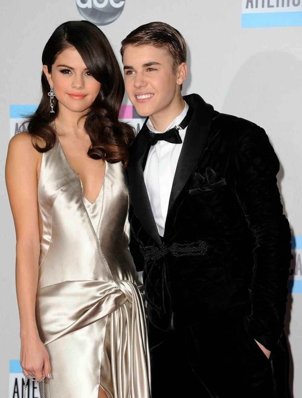 Justin Bieber i svart kostym och Selena Gomez i guldig klänning