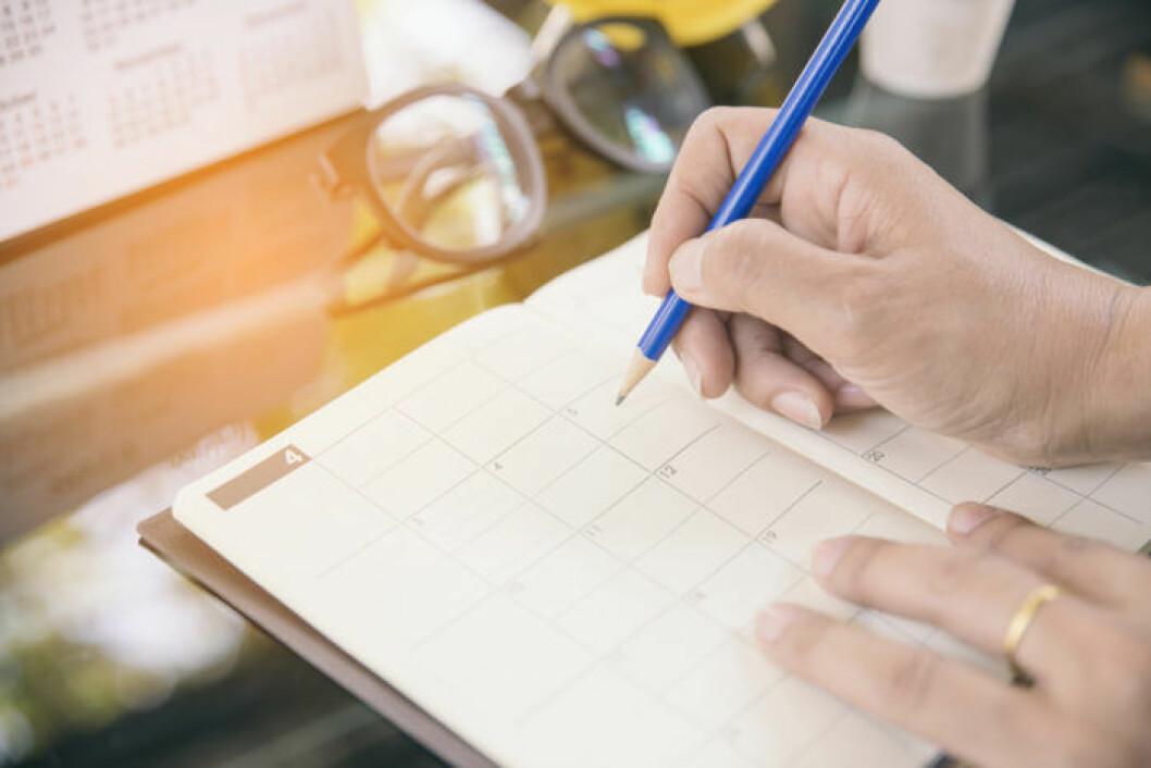 Kvinna skriver i en kalender.