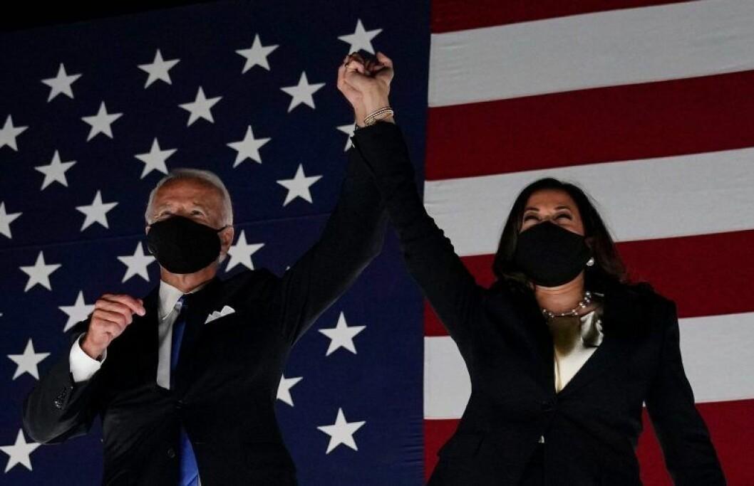 Joe Biden och Kamala Harris har ansiktsmask och sträcker upp händerna i luften