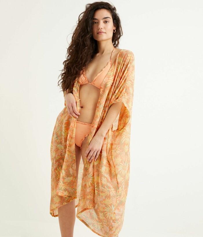 Modell med orange bikini och en tunn kaftan över. Mönstrad med blommor i gula och orangea detaljer.