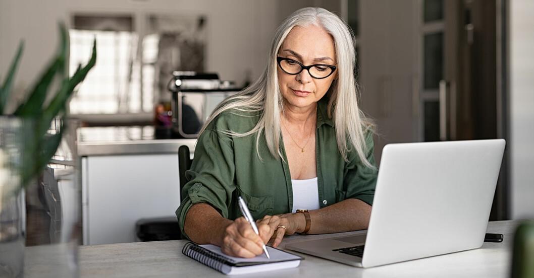 en kvinna som sitter vid ett bord och skriver