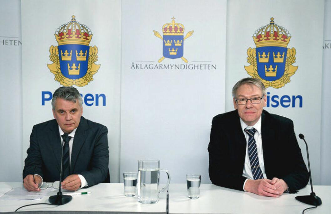 Två män i kostym sitter vid ett bord med mikrofoner och vattenglas.