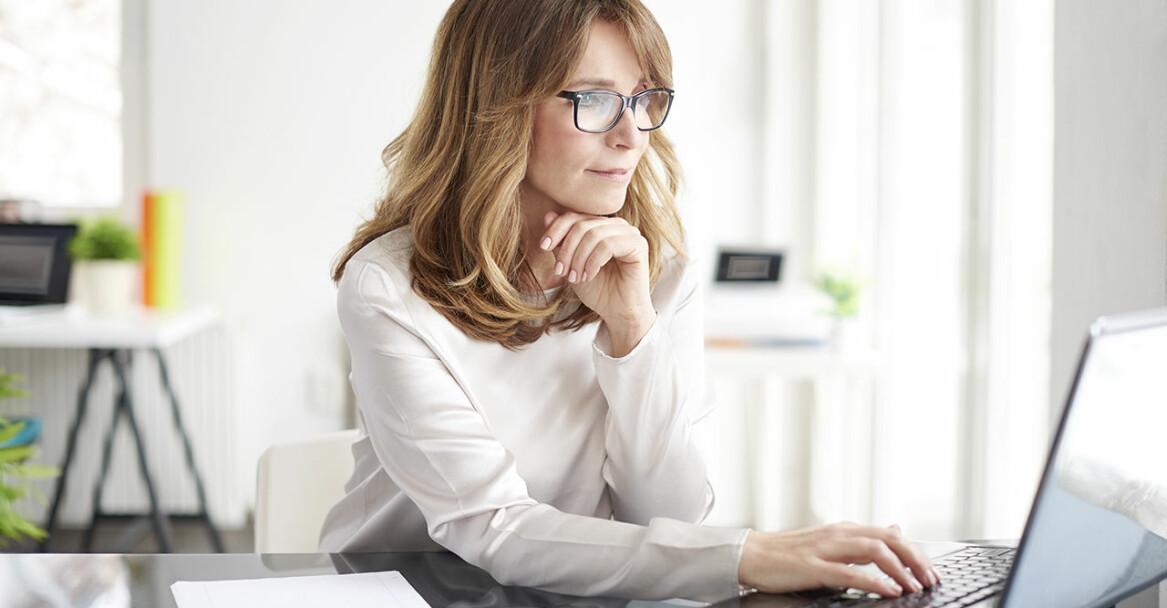 Kvinna sitter framför sin laptop