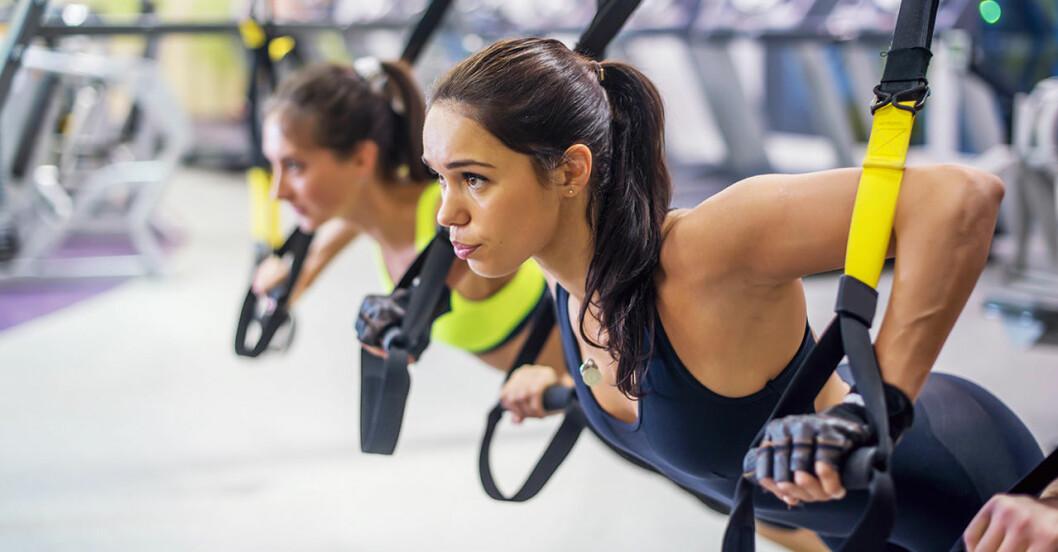 Två kvinnor som tränar med hjälp av trx-band