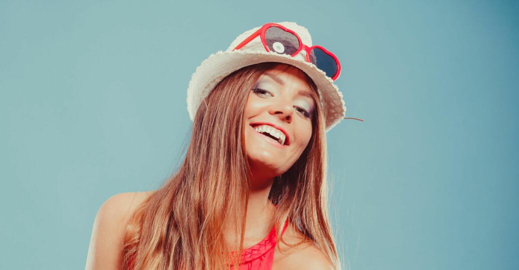 solbrun skrattande kvinna med solglasögon