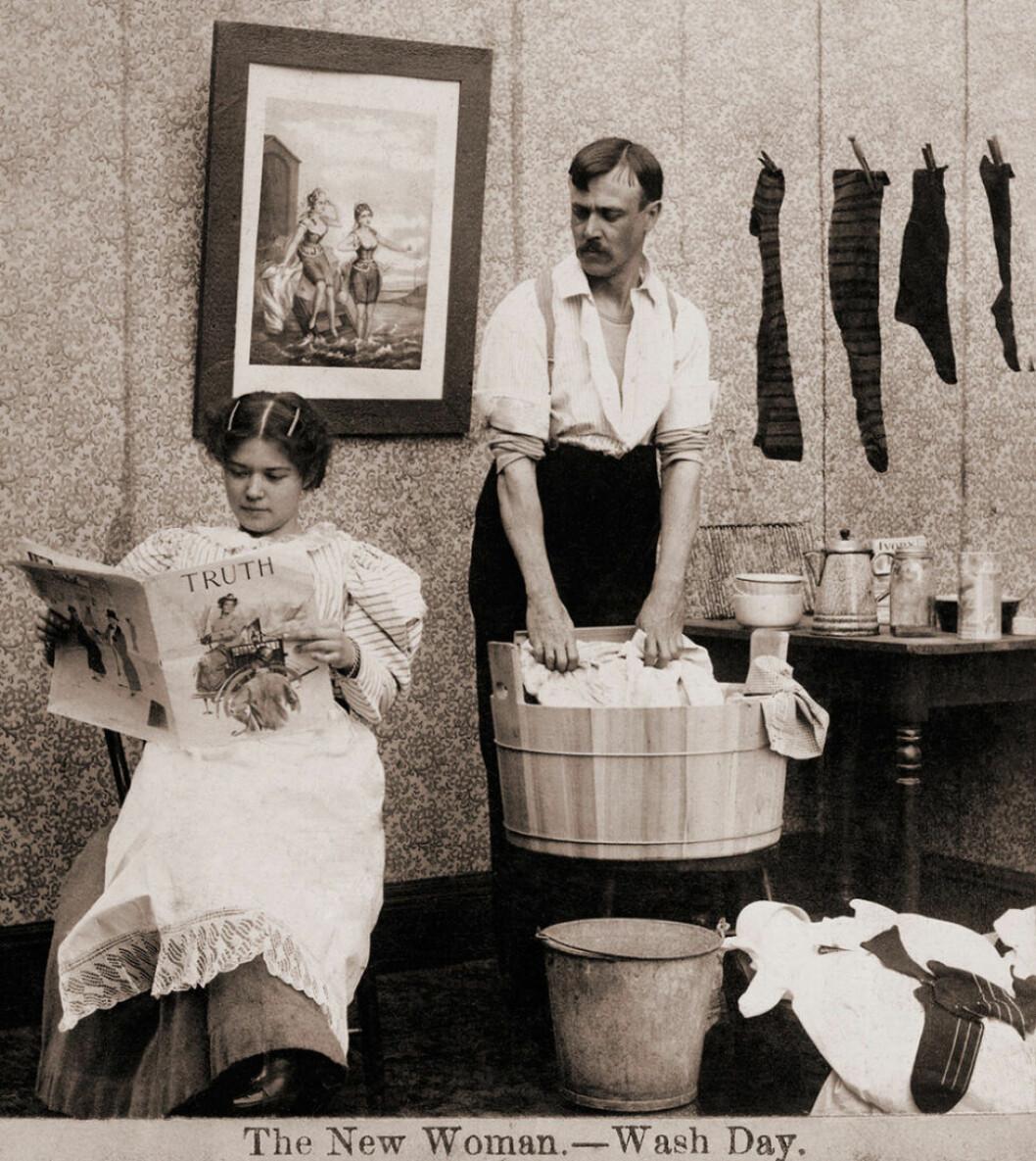 Kvinna läser tidningen samtidigt som mannen tvättar kläder.