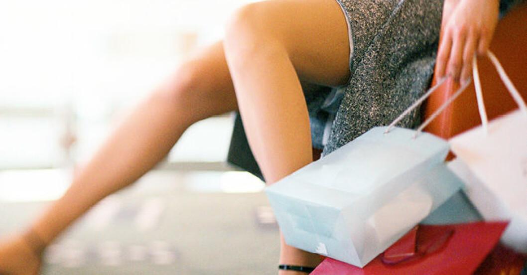 kvinna sittande i fåtölj med shoppingpåsar
