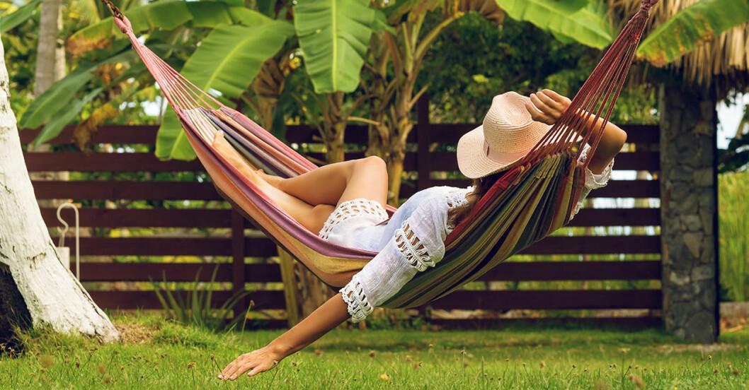 Kvinna slappar i hängmatta med solhatt
