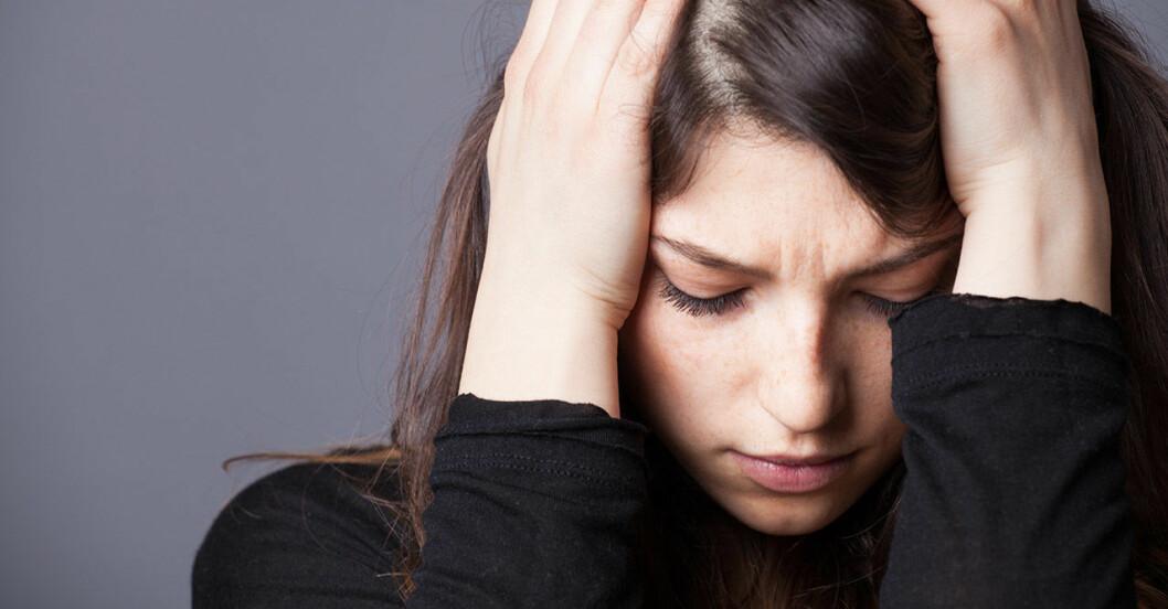 Kvinna med huvudet i händerna mår dåligt och lider av ångest