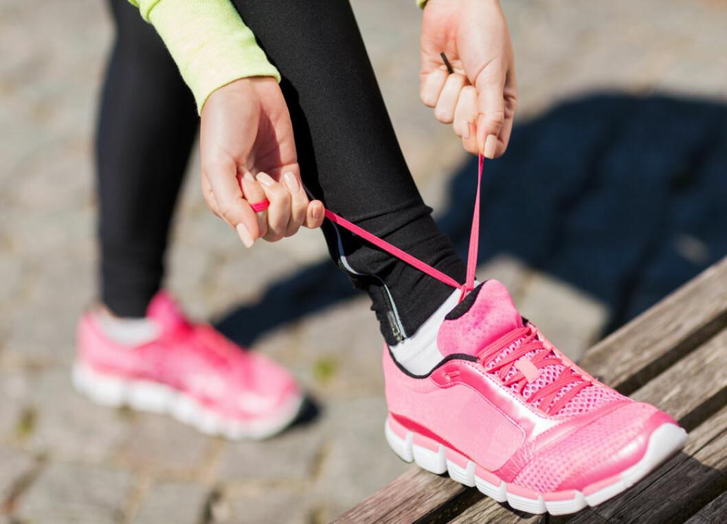 Kvinna som knyter sina joggingskor