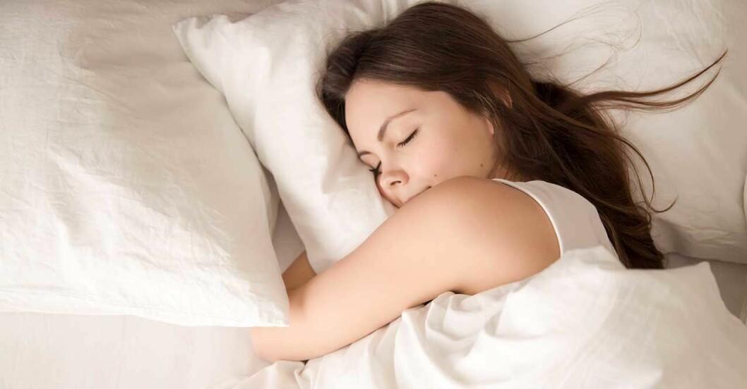 Kvinna som sover i säng utan sömnproblem