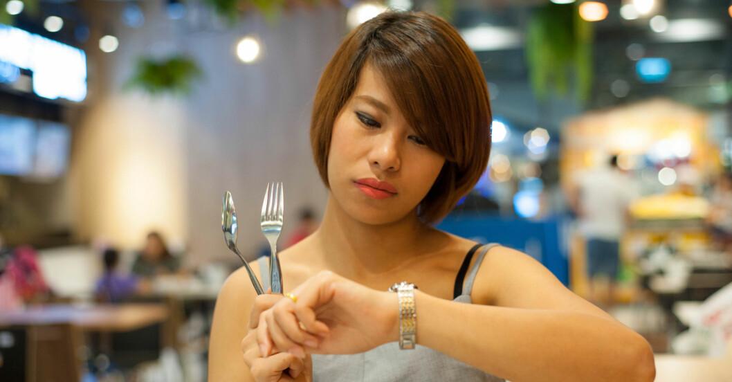 Kvinna som tittar på klockan och håller i bestick