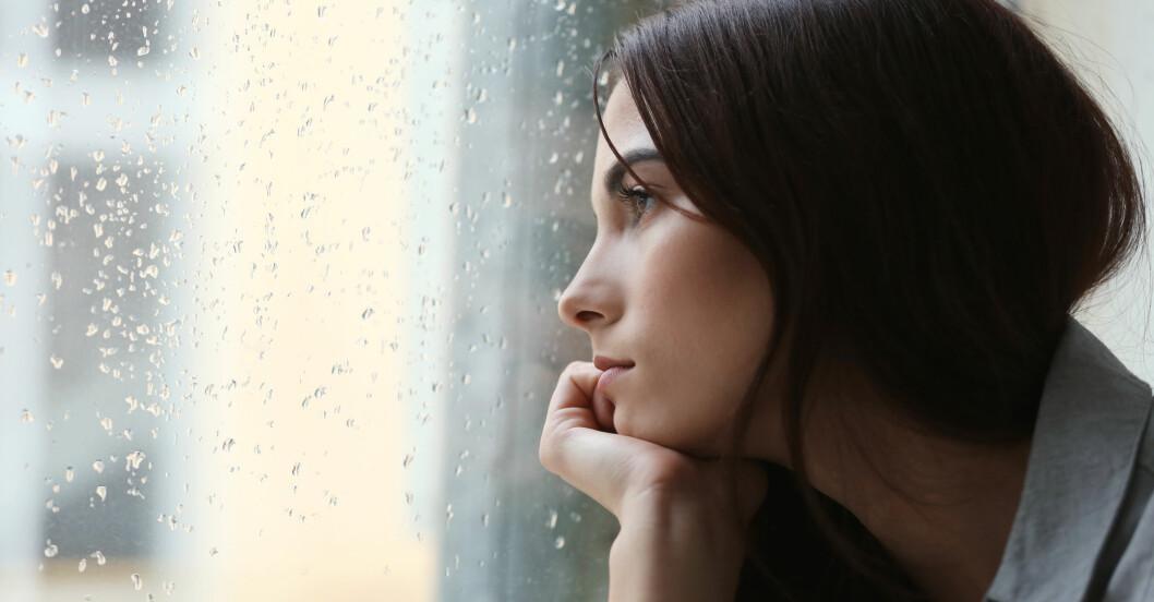 Kvinna tittar ut på regn genom fönster
