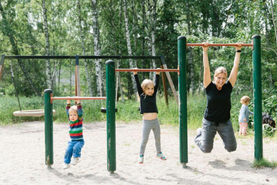 En mamma som tränar i en lekpark tillsammans med sina två barn.