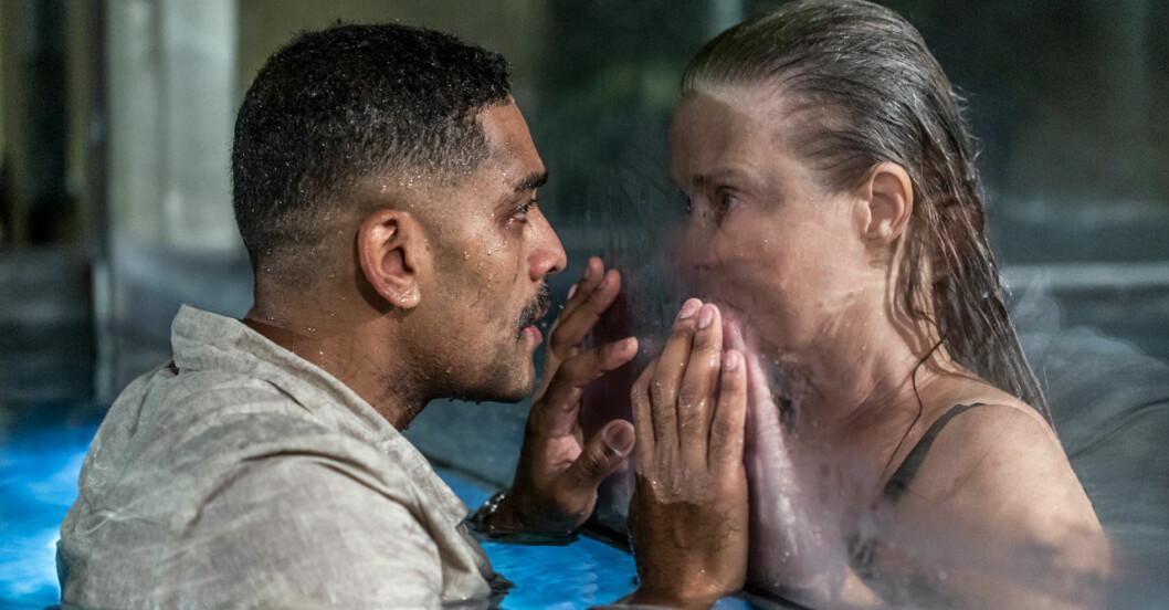 Alexander Karim och Lena Endre i en pool med glasvägg