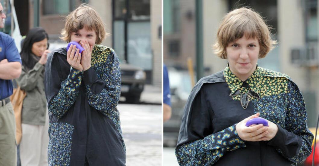 Lena Dunham döljer sina tänder genom att knipa ihop munnen.