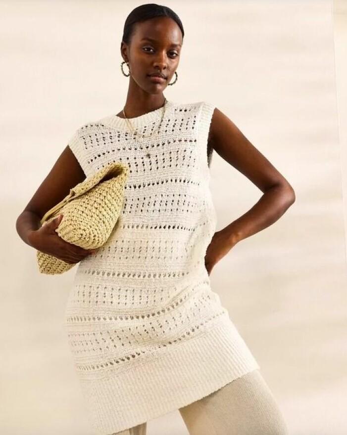Off-white stickad klänning utan ärmar. Fotad på modell. Stylad med byxor och en kuvertväska. Stickad klänning från Lindex.