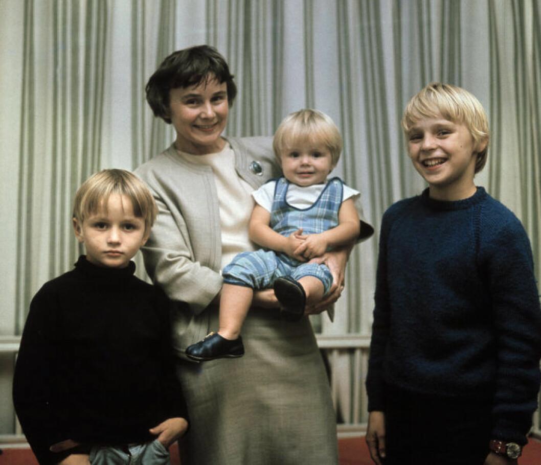 Lisbeth Palme håller sonen Mattias i famnen och Mårten och Mattias står bredvid henne på varsin sida