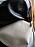 Närbild på liten, vit handväska i skinn med struktur. Väska från Little liffner.