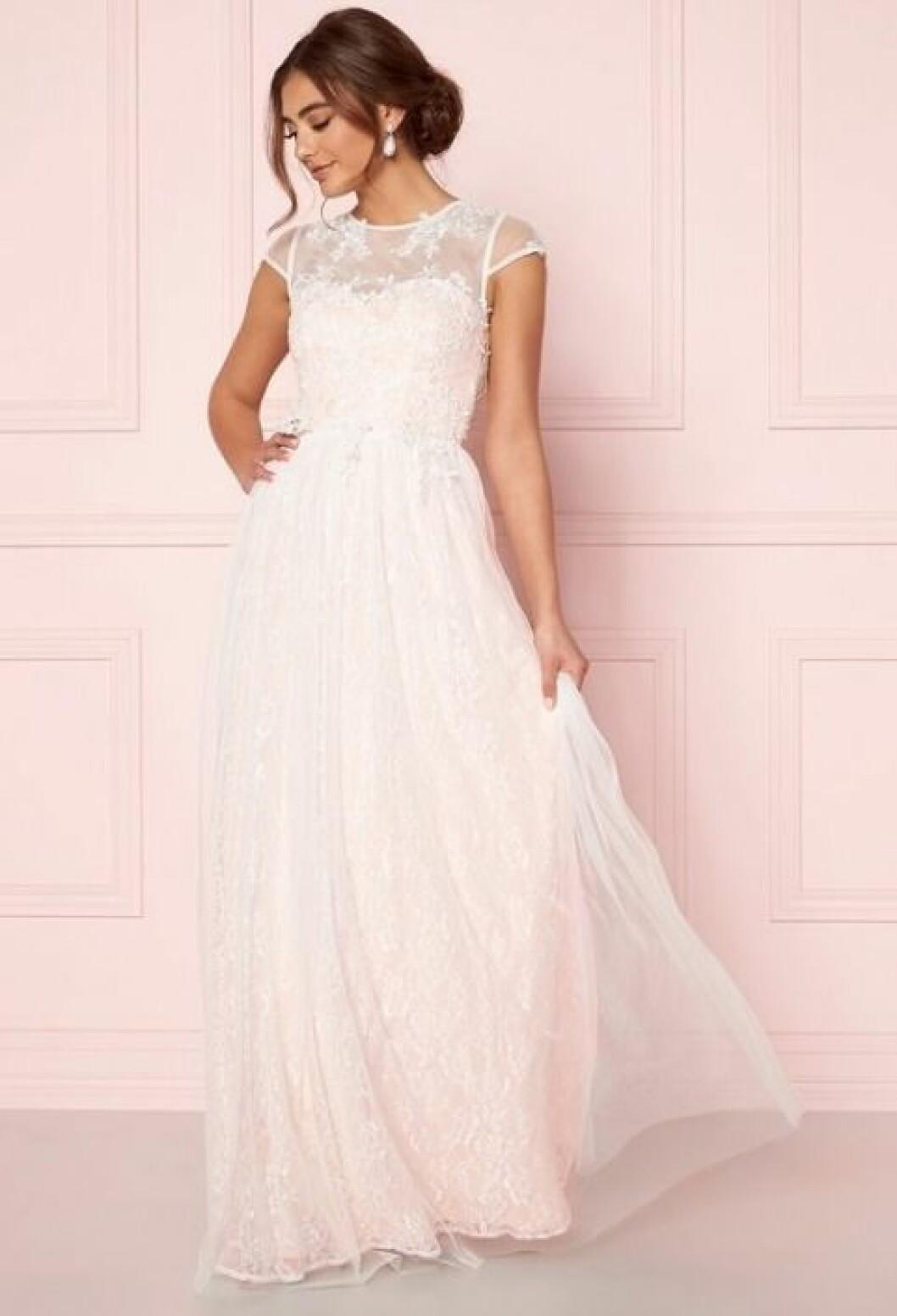 En bild på en ljusrosa brudklänning med spetsdetaljer från Bubbleroom.