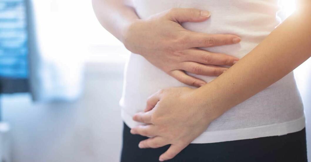 Kvinna håller sig för magen som kurrar