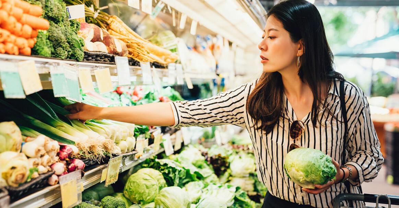 Kvinna står i butik och plockar grönsaker