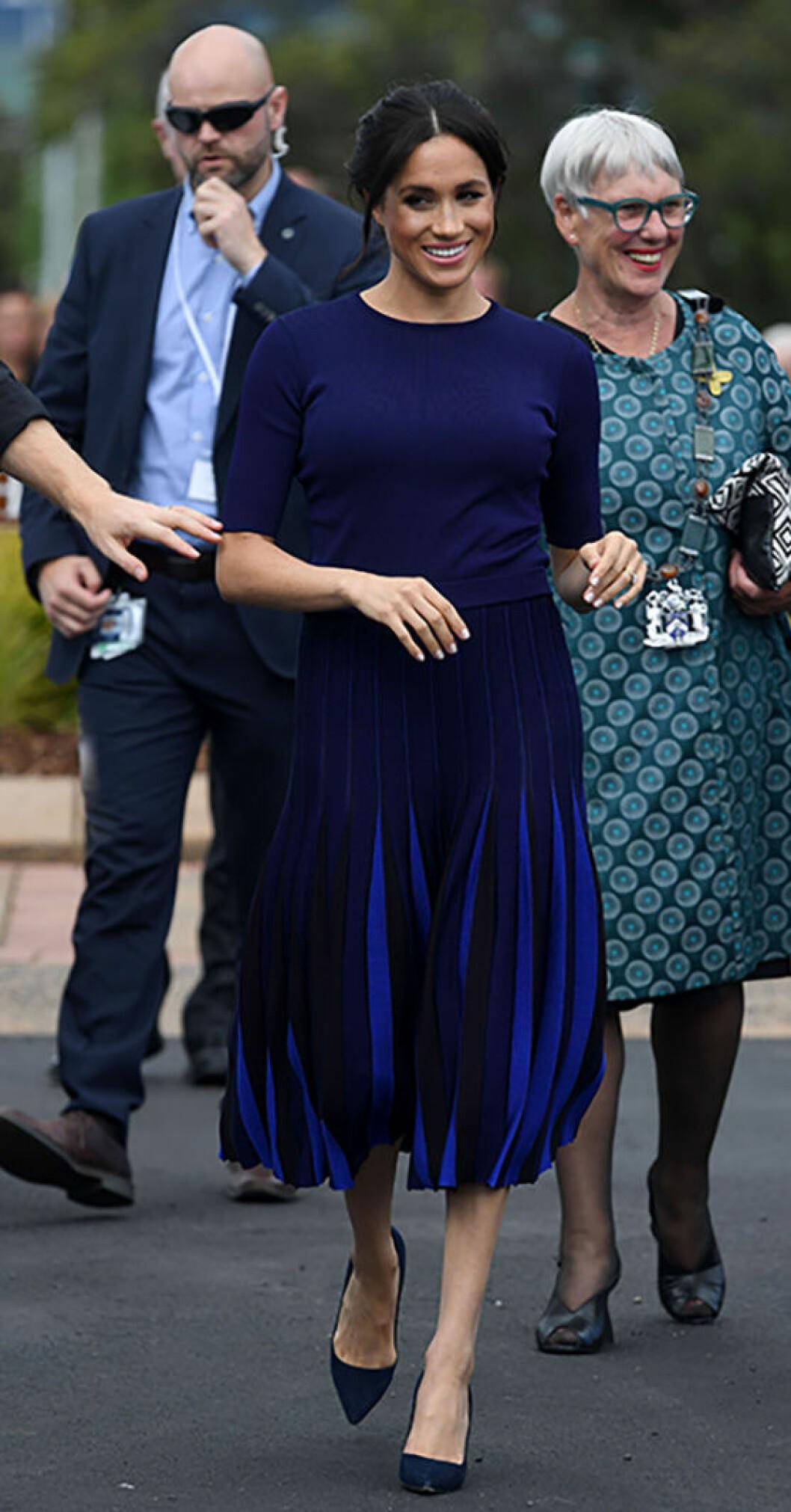 En bild på den brittiska hertiginnan Meghan Markle i mörblå blus och kjol under sin första kungliga utrikesresa.