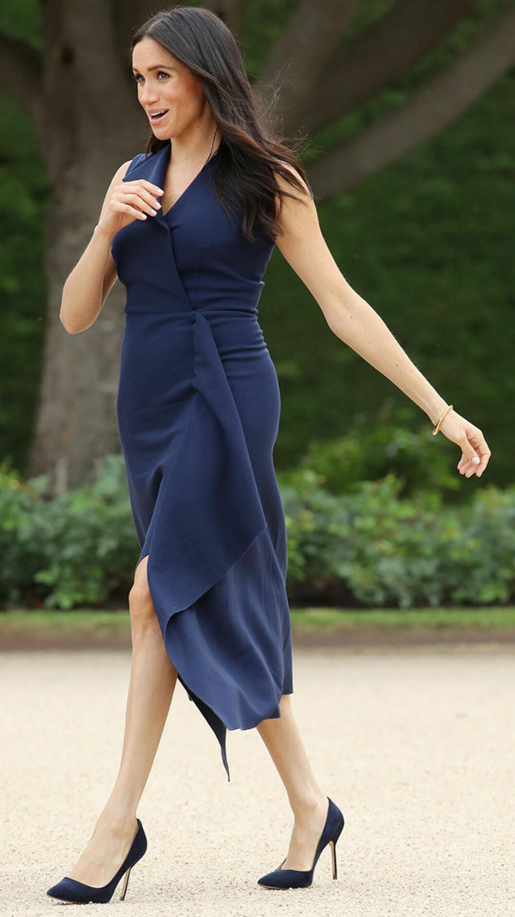 En bild på den brittiska hertiginnan Meghan Markle i en mörkblå klänning.