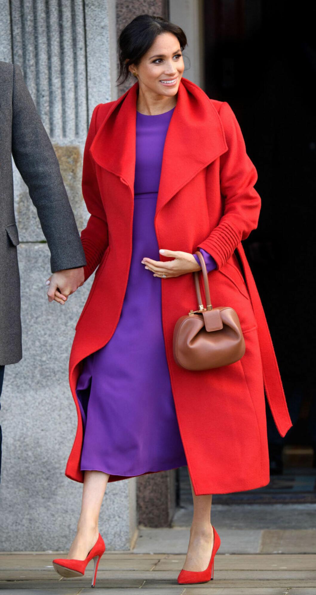 Meghan Markle i lila klänning och röd kappa