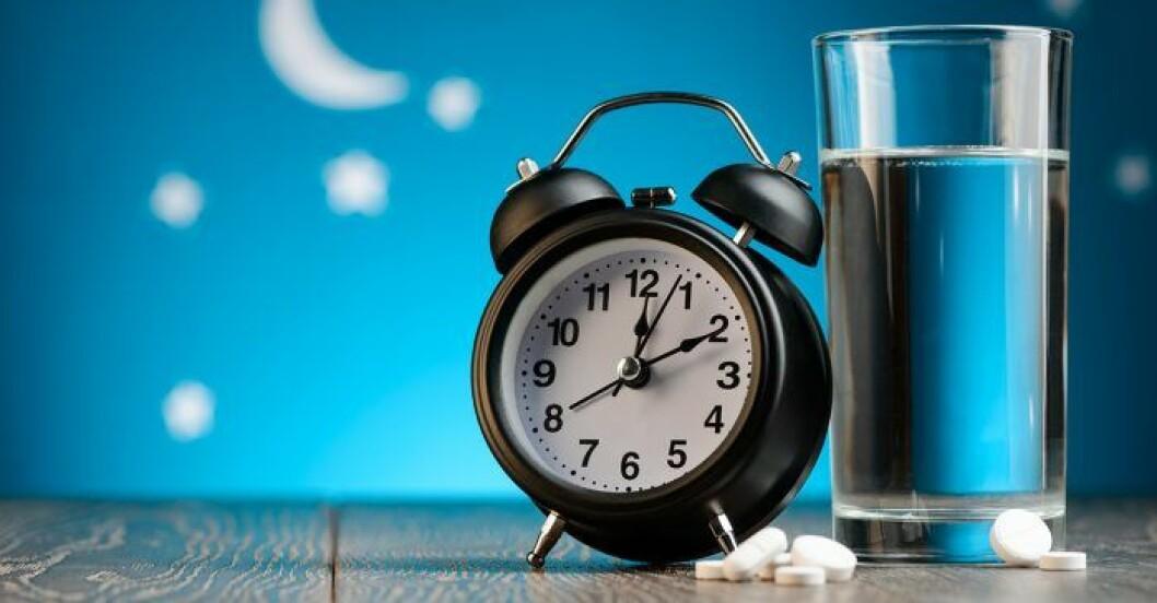 En väckarklocka, sömnpiller och ett glas vatten på nattduksbord