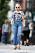 Skådespelerskan Michelle Williams i blommig topp med trekvarts långa ärmar, raka, blå jeans med hög midja och som är fransiga nertill, vävd tygväska i beige och bruna träskor. Hon bär solglasögon och har hörlurar i öronen.