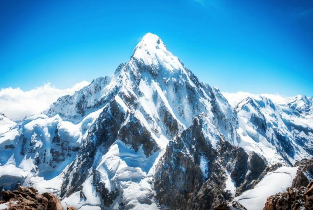 höga berg med snö på och blå himmel
