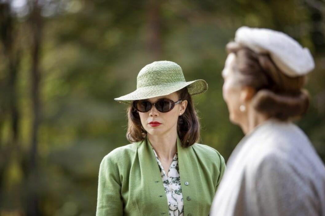 hedda stiernstedt i grön hatt, grön kappa och mörka solglasögon
