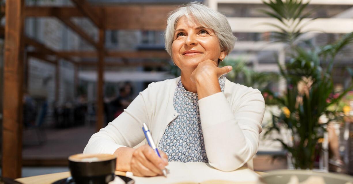 en kvinna med grått kort hår håller ena handen under hakan och tittar lite uppåt. Med andra handen skriver hon på ett papper.