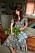 Helena Christensen i en av grön klänning med blommönster på. I knät ligger en stor bukett med ljusblå blommor och på fötterna har hon gladiatorsandaler med remmar i beige. Klänning från Odd Molly.